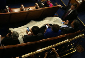 Members stayed warm and cuddly with a blanket and smartphones in the House chamber before President Obama's speech.  Credit Doug Mills/The New York Times